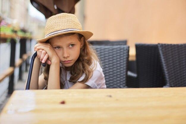 Retrato de menina cansada criança infeliz entediado sentado no café ao ar livre