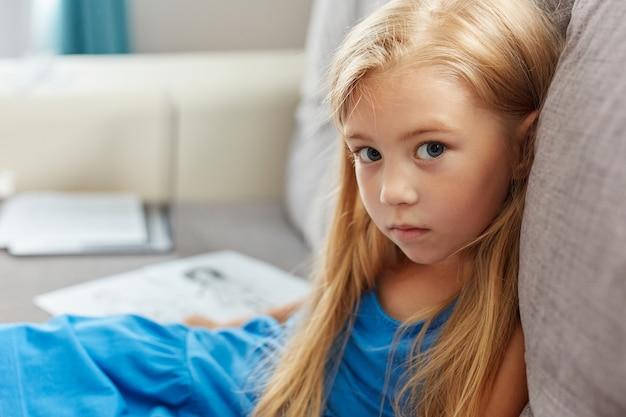 Retrato de menina caucasiana com vestido, sentada no sofá na sala
