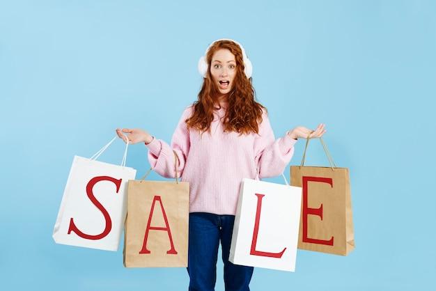 Retrato de menina chocada segurando sacolas de compras