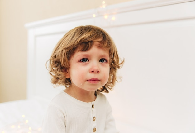 Retrato de menina chorosa. pequena menina bonita está chorando.indoor.curly cabelo e olhos azuis.