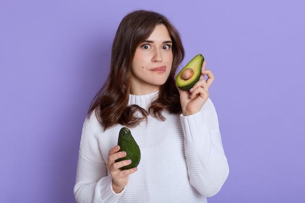Retrato de menina com aparência agradável, mulher com duas partes de abacate nas mãos isoladas sobre parede lilás, fazendo careta enquanto mostra a língua, quer provar frutas exóticas.