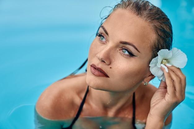 Retrato de menina com cabelo molhado e flor.
