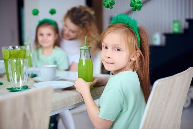 Retrato de menina com coquetel à mesa