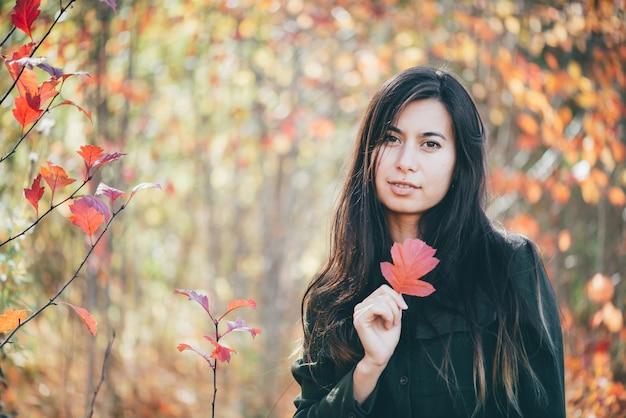 Retrato de menina com folha vermelha em fundo de bokeh de outono.