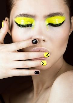 Retrato de menina com maquiagem amarela e preta, arte criativa das unhas