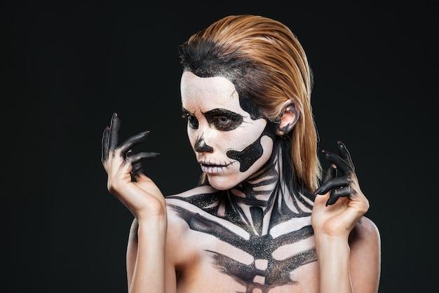 Retrato de menina com maquiagem assustadora de halloween sobre fundo preto