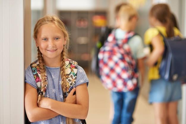 Retrato de menina com mochila no corredor da escola