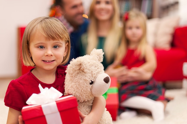 Retrato de menina com seu ursinho de pelúcia e família na época do natal