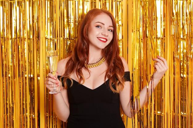 Retrato de menina com taça de champanhe, posando contra a parede decorada com enfeites de ouro, senhora de vestido preto e colar.