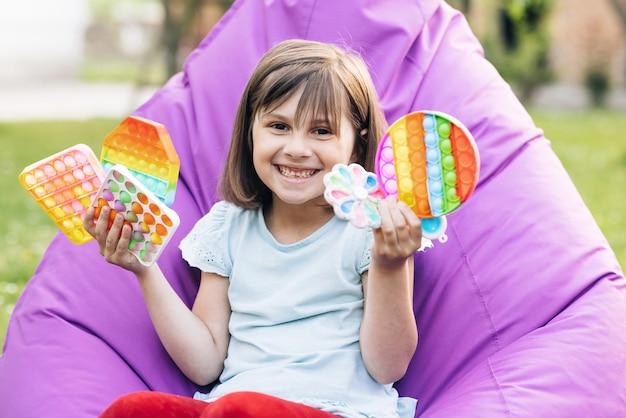 Retrato de menina com um brinquedo popit moderno colorido e brilhante pop it brinquedo covinha simples