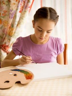 Retrato de menina concentrada desenhando na tela com tintas a óleo