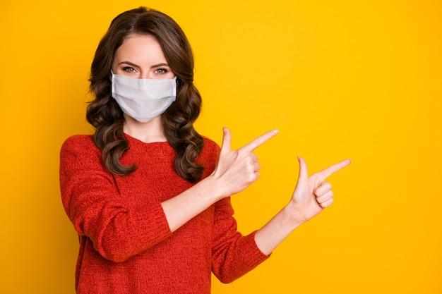 Retrato de menina confiante positiva apontar dedo indicador copyspace maneira direta anúncios secretos promoção usar jumper de boa aparência máscara médica isolada brilho brilhante cor de fundo