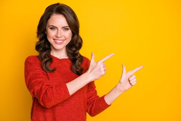 Retrato de menina confiante positiva apontar o dedo indicador copyspace maneira direta anúncios promoção usar jumper de boa aparência isolado sobre fundo de cor de brilho brilhante