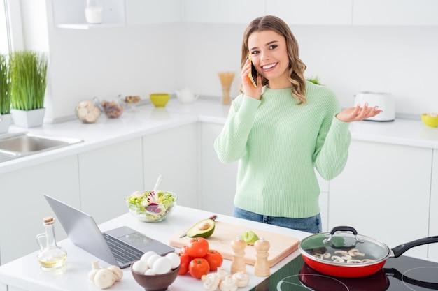 Retrato de menina cozinhando um prato de comida vegetariana usando laptop falando no telefone