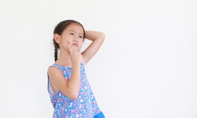 Retrato de menina criança asiática, expressão pensando e apontando o dedo indicador na bochecha