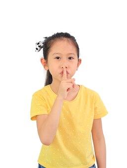 Retrato de menina criança asiática mostra sinal shh isolado no fundo branco.