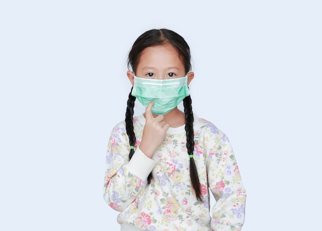 Retrato de menina criança asiática usando máscara protetora médica e aponta o dedo para a máscara no fundo branco
