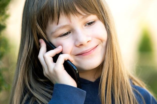 Retrato de menina criança bonita com cabelos longos, falando no celular. criança do sexo feminino se comunicar usando o smartphone. conceito de comunicação de crianças.