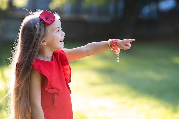 Retrato de menina criança bonita feliz apontando o dedo ao ar livre, aproveitando o dia quente de verão ensolarado.