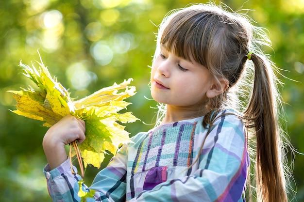 Retrato de menina criança bonita feliz segurando um monte de folhas de árvores caídas na floresta de outono.