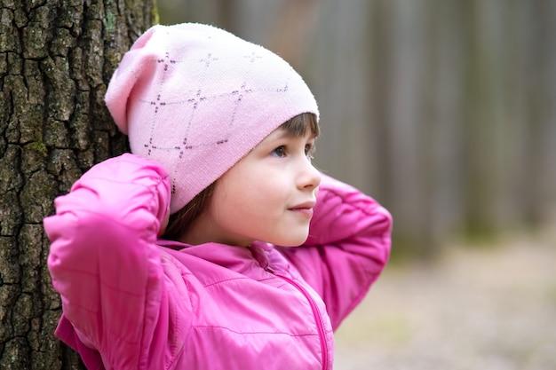 Retrato de menina criança bonita vestindo jaqueta rosa e boné inclinando-se para uma árvore na floresta, aproveitando o dia de sol quente no início da primavera ao ar livre.
