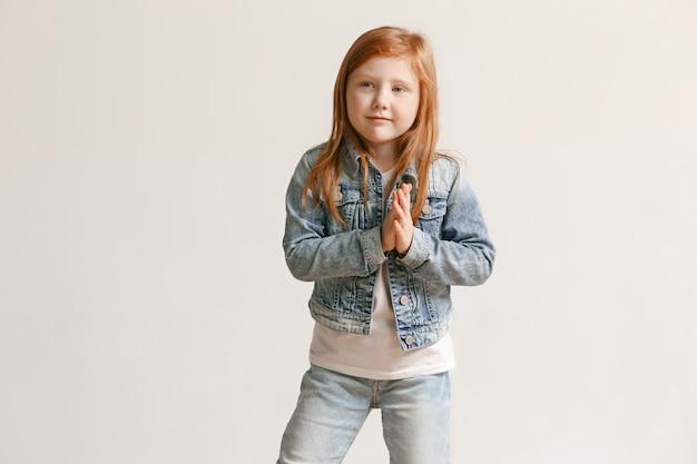 Retrato de menina criança bonitinha em roupas jeans elegantes, olhando para a câmera e sorrindo