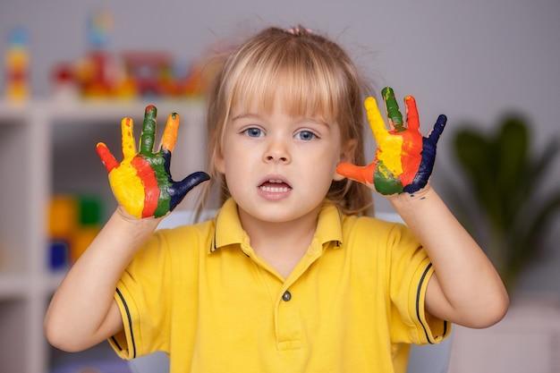 Retrato de menina criança com rosto e mãos pintadas em casa