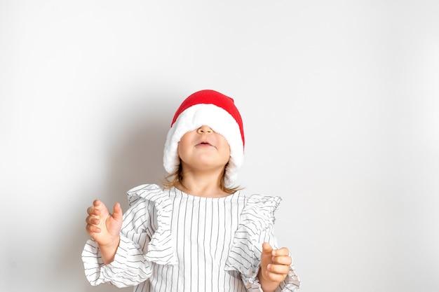 Retrato de menina criança de chapéu vermelho no natal. conceito surpresa