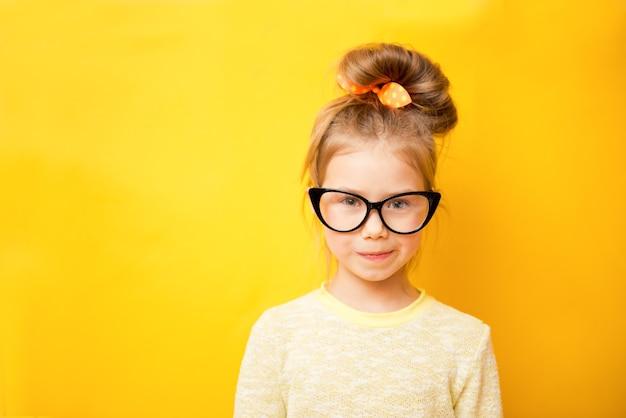 Retrato de menina criança de óculos em um fundo amarelo. copie o espaço