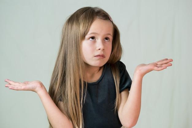 Retrato de menina criança, encolher os ombros os ombros tornando inocente eu não sei expressão.