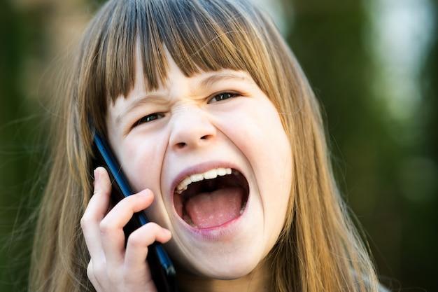 Retrato de menina criança irritada com cabelos longos, falando no celular. criança feminina discutindo no smartphone. conceito de comunicação de crianças.
