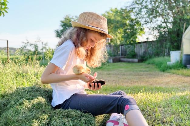 Retrato de menina criança segurando pintinhos recém-nascidos nas mãos, dia ensolarado de primavera no jardim