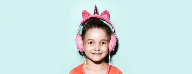 Retrato de menina criança sorridente, ouvindo música com fones de ouvido no fundo do aqua menthe