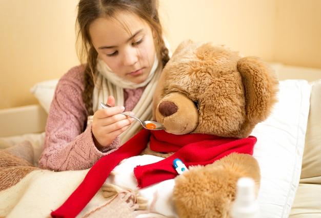 Retrato de menina dando remédios para o ursinho de pelúcia