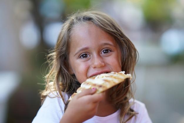 Retrato de menina de 4 anos comendo um pedaço de pizza