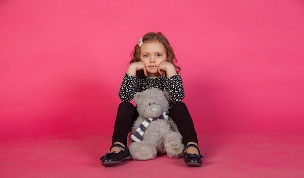 Retrato de menina de 5 a 6 anos em um vestido em fundo rosa com a inscrição do ursinho de pelúcia para você