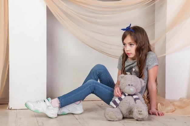 Retrato de menina de 7 a 8 anos em roupas casuais perto da lareira com a inscrição do ursinho de pelúcia para você