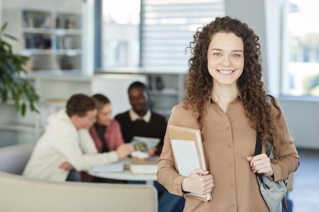 Retrato de menina de cabelo encaracolado e sorrindo enquanto está na biblioteca da faculdade com pessoas trabalhando em segundo plano,