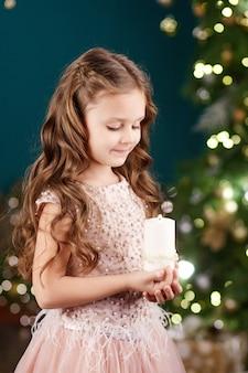 Retrato de menina de cabelos compridos bonitinho no vestido em fundo de luzes