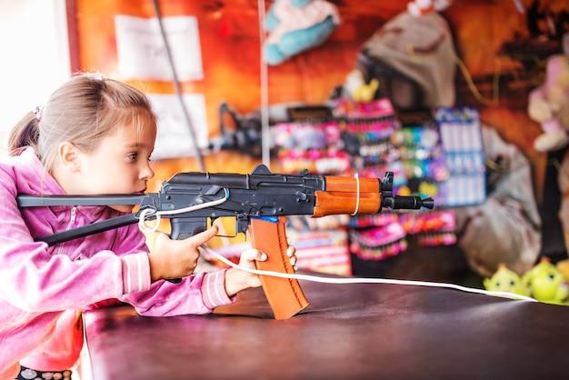 Retrato de menina de suéter rosa atira de arma de brinquedo para crianças.