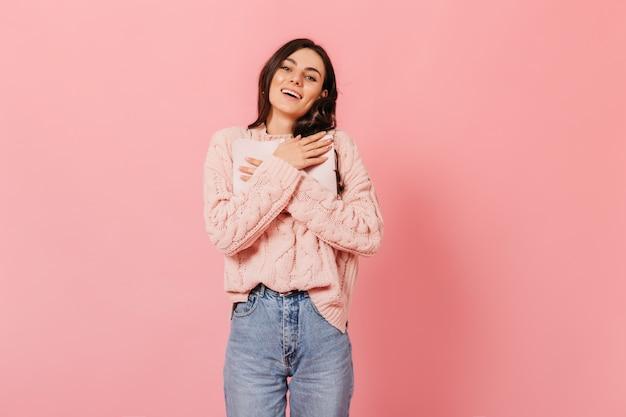 Retrato de menina de suéter rosa e jeans de mãe em fundo isolado. morena de olhos azuis com covinhas nas bochechas pressiona um diário importante contra o peito.