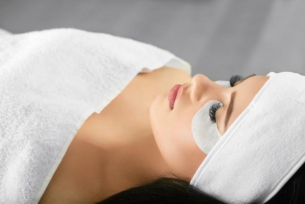 Retrato de menina deitada durante o procedimento de extensão de cílios de salão