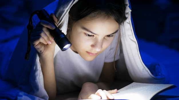 Retrato de menina deitada sob o cobertor à noite e lendo o livro com uma tocha leve.