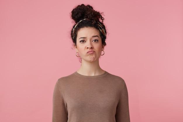 Retrato de menina descontente com coque de cabelo encaracolado escuro. usando bandana, brincos e suéter marrom. tem maquiagem. rosto irônico em desgosto