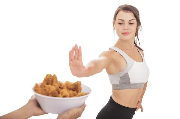 Retrato de menina desportiva saudável em processo de dieta rejeitando uma tigela de frango frito