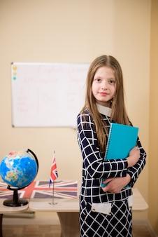 Retrato de menina diligente olhando para a câmera na sala de aula.