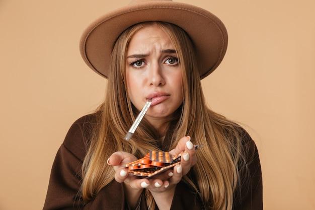 Retrato de menina doente caucasiana com chapéu segurando um monte de comprimidos com termômetro na boca isolado em bege