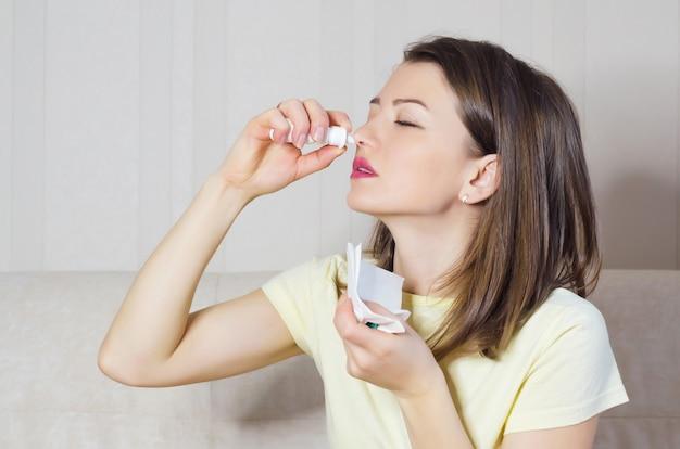 Retrato de menina doente com coriza, rinite, alergias, resfriados. mulher detém spray médico na mão. foco suave