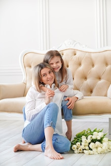 Retrato de menina e sua mãe na sala de estar