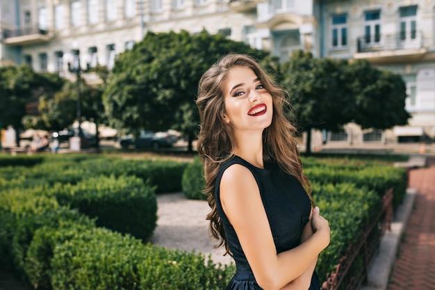 Retrato de menina elegante, com cabelos longos e lábios vínicos no pátio. ela usa vestido preto e sorri.